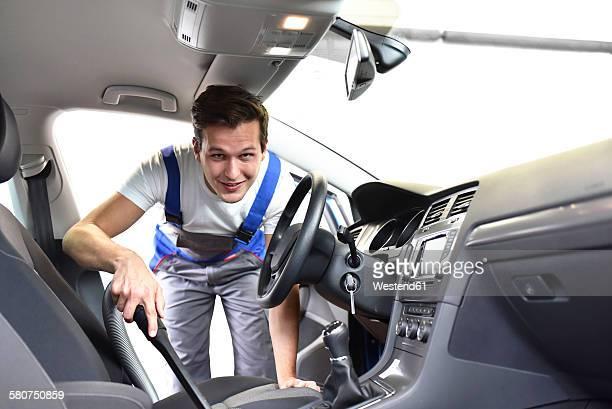 Man hoovering car interior