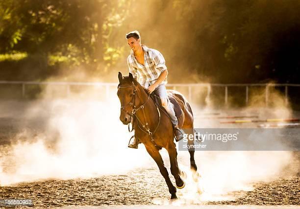 Homme Monter à cheval au coucher du soleil.