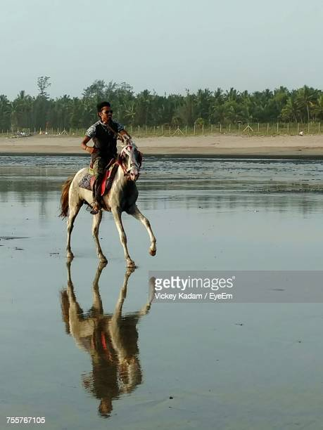 Man Horseback Riding On Shore At Beach