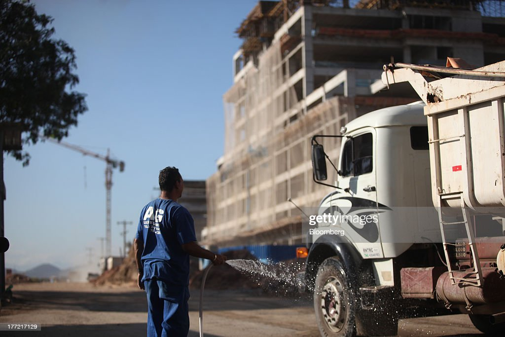 A man hoses down a truck at the Metropolitano Barra Shopping center under construction in Rio de Janeiro, Brazil, on Wednesday, Aug. 21, 2013. Latin America's largest economy created 7,154 manufacturing jobs and 4,899 construction jobs in July, down from 24,718 and 25,433 new posts a year ago. Photographer: Dado Galdieri/Bloomberg via Getty Images