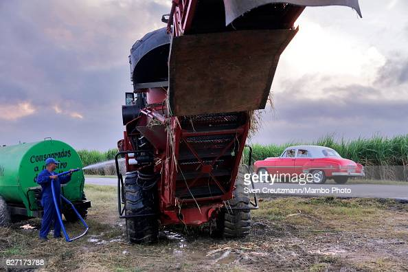 A man hoses off a harvest machine during the zafra the sugarcane harvest in the eastern province of Camagüey on December 1st in Camagüey Cuba...
