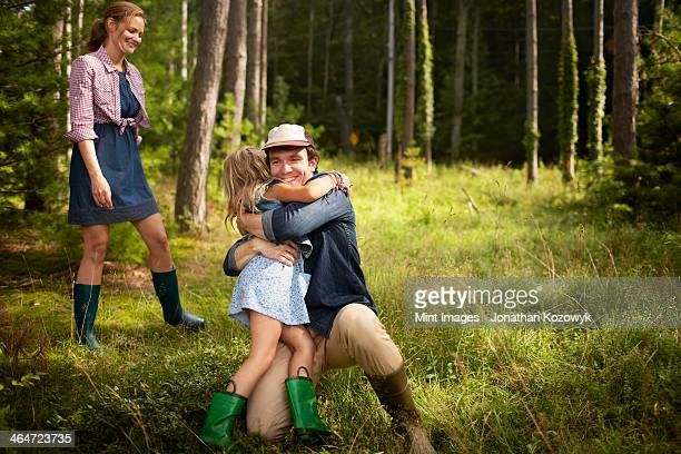 A man hugging a young child. A family on a woodland walk.