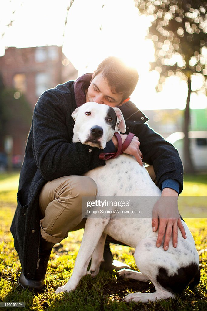 Man hugging dog in park : Stock Photo