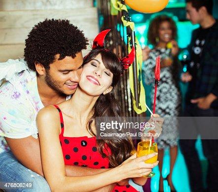 Man hugging girlfriend at party : Stock Photo