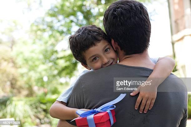 Homme embrassant souriant jeune garçon tenant un cadeau en plein air