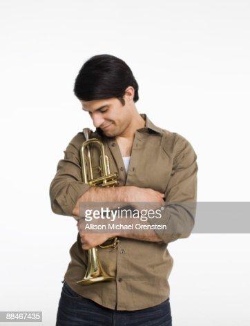 Man hugging trumpet