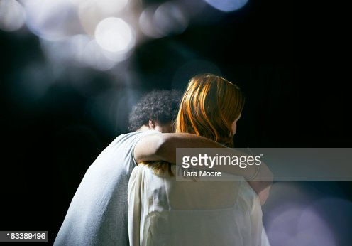man hugging woman with lens flare