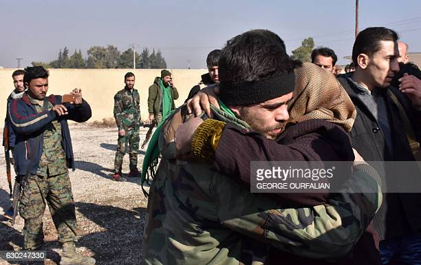TOPSHOT A man hugs a woman as buses evacuating civilains from Fuaa and Kafraya two Shiite villages under rebelsiege on the northern outskirts of...