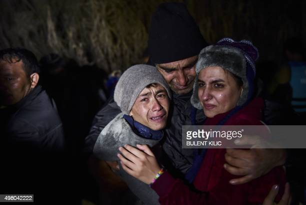 A man hugs his daughter and son as migrants and refugees arrive on the Greek island of Lesbos after crossing the Aegean Sea from Turkey on November...