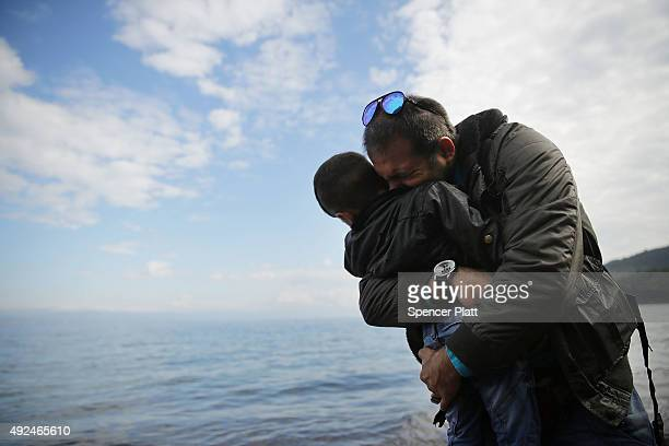 A man hugs his son moments after arriving on the island of Lesbos in a raft from Turkey with other Iraqi and Syrian refugees October 13 2015 in...