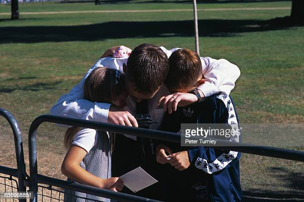 A man hugs two children as they mourn the death of Diana Princess of Wales from injuries sustained in an automobile accident on August 31 1997 in...