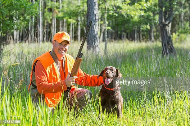 Man hunting with shotgun kneeling next to retriever