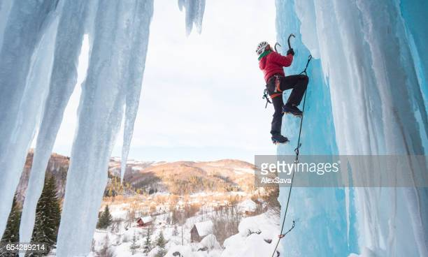 Man ice climbing on frozen waterfall