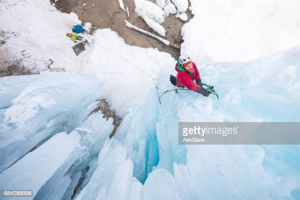 Man ice climbing on vertical icicle using ice axe
