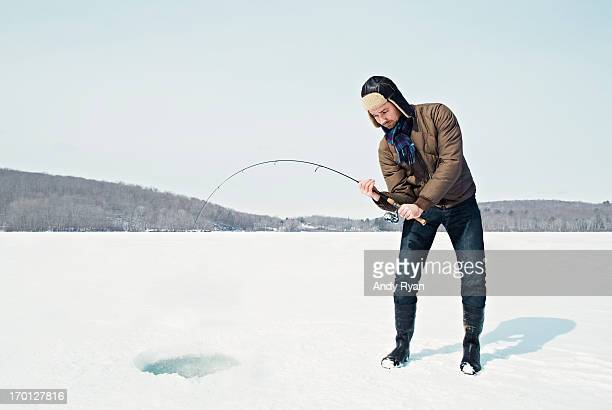 Man Ice Fishing on Frozen Lake.