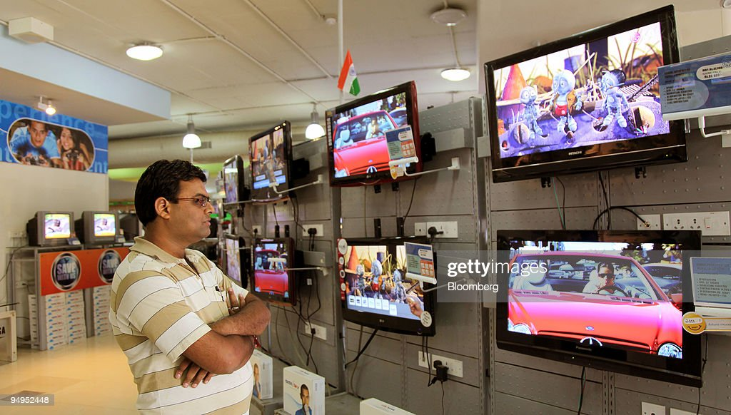 A man identified only as Kanaiya looks at new LCD televisions at an eZone retail showroom in the Jayanagae area in Bangalore India on Saturday Aug 29...