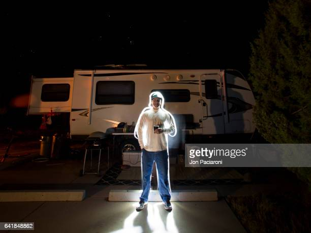 Man Illuminated in Light Standing near a Mobile Home Holding a Beer