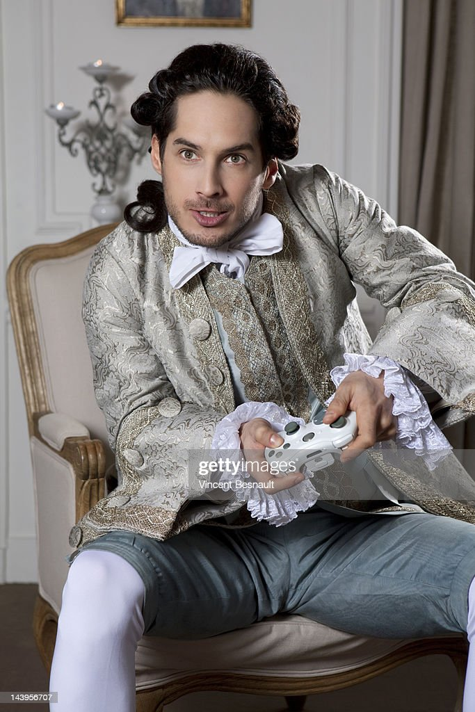 A man in 18th century garb using a games console