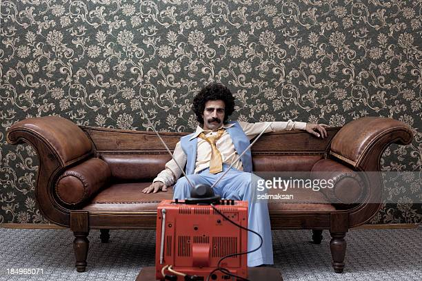 Man In 1970s Style Sitting On Sofa Watching Television
