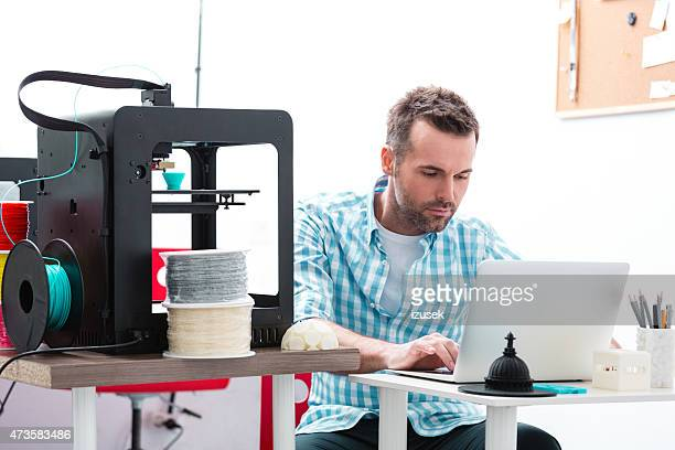 Man in 3D printer office using laptop