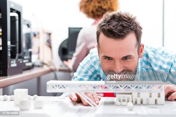 Homme de bureau en regardant printings imprimante 3D