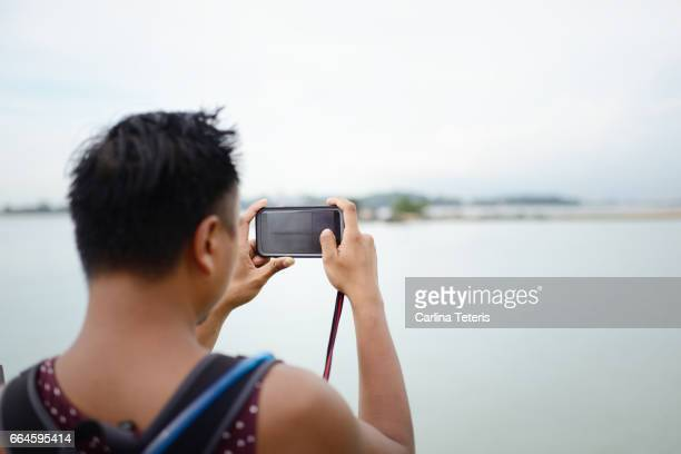 Man in a backpack taking photos of a low tide seashore