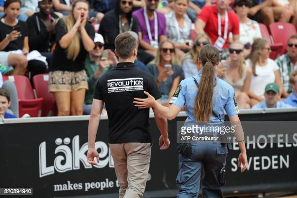 A man in a black tshirt with neonazi slogans is walked off the court after raising his arm in a Nazilike salute during the ATP tennis tournament...