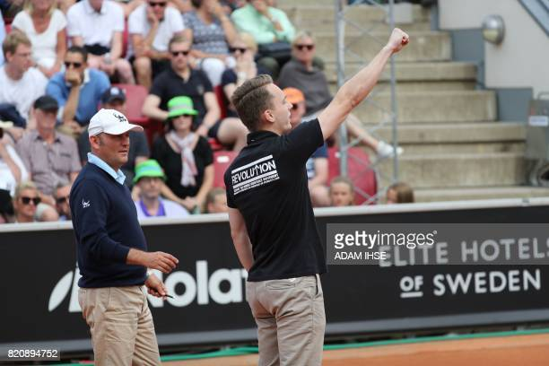 A man in a black tshirt with neonazi slogans raises his arm in a Nazilike salute after walking on the court during the ATP tennis tournament Swedish...