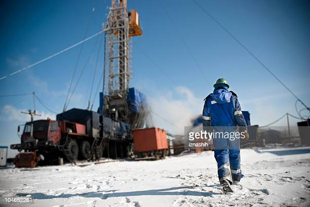 Man in a blue jumpsuit walking onto snowy construction site