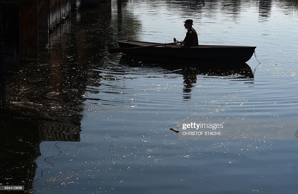 A man in a boat prepares to take part in a Corpus Christi procession at the lake Staffelsee in Seehausen near Murnau, southern Germany, on May 26, 2016. / AFP / CHRISTOF