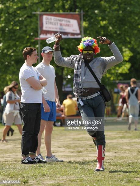 A man in a brightly coloured wig dancing at the As One In The Park festival in Victoria Park east London