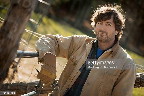 Ein Mann in Braune Jacke, die Arbeit Handschuhe Schiefer