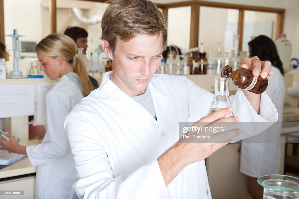 Man in a busy laboratory measuring liquids : Stock Photo