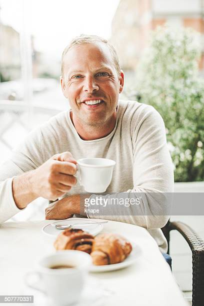Man in a cafe having a coffee break with croissants