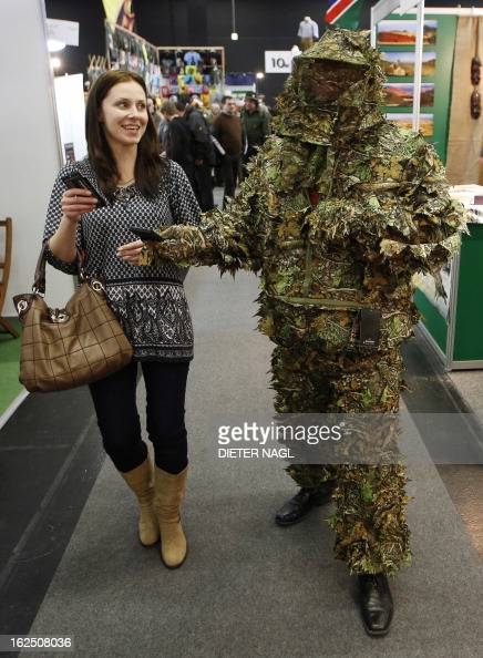 A man in a camouflage suit walks with his girlfriend at the 'Hohe Jagd' hunting fair on February 24 2013 in Salzburg AFP PHOTO/DIETER NAGL