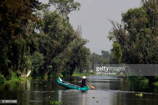 A man in a canoe is seen in a water channel amid the floating gardens of Xochimilco a UNESCO World Heritage Site during a symposium on biodiversity...
