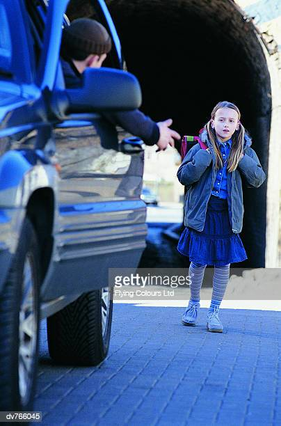 Man in a Car Beckoning an Apprehensive Girl Standing in a City Street
