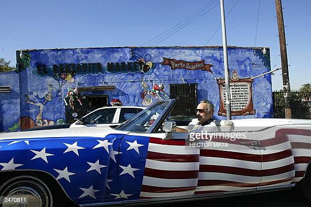 A man in a car decorated as an American flag drives by past party supply store 'El Centavito Market' during the parade celebrating the independence...
