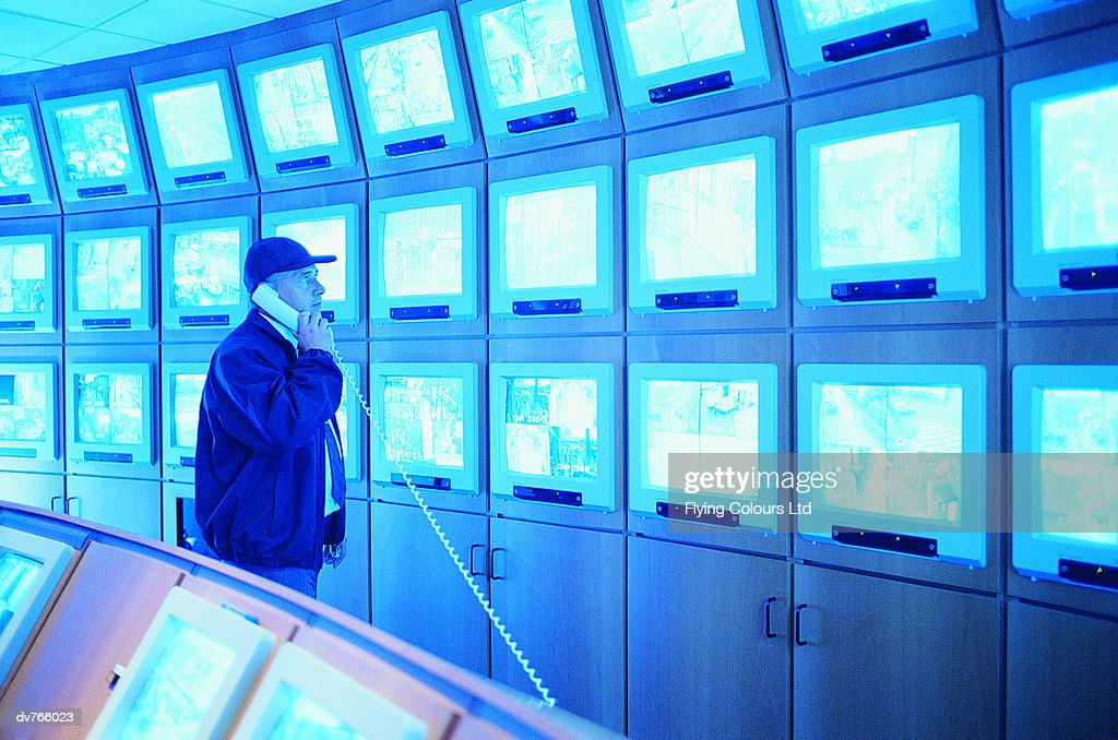 Man in a Control Room Looking at a Large Group of Surveillance TV Screens : Stock Photo