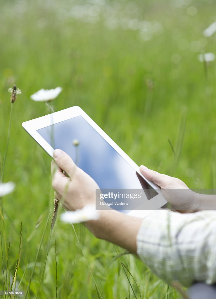 Man in a country meadow reading from a tablet : Stock Photo