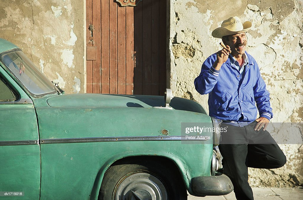 Man in a Cowboy Hat, Holding a Cigar and Smiling, Stands By a Parked Car in Havana, Cuba : Stock Photo
