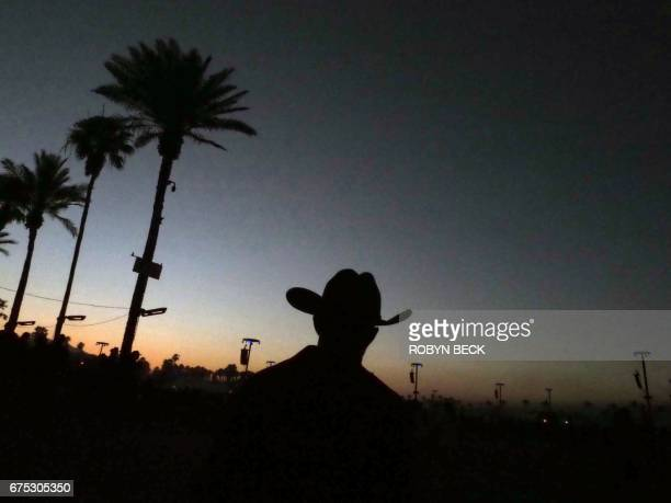 A man in a cowboy hat walks on the last day of the 2017 Stagecoach Country Music Festival at the Empire Polo Club on April 30 2017 in Indio...