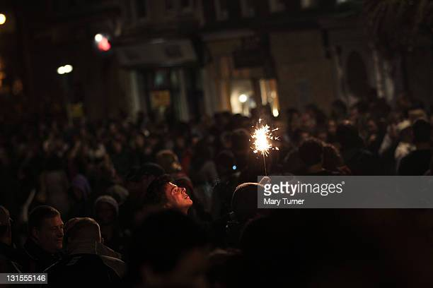 A man in a crowd holds up a sparkler during the Lewes annual bonfire night parade on November 05 2011 in Lewes England Thousands of people attend the...
