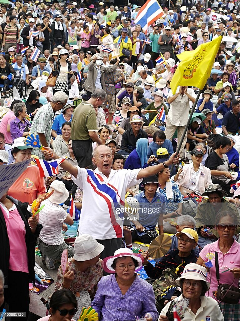 A man in a crowd of thousands waves the flag of the Thai King during an anti government protest on November 24, 2012 in Bangkok, Thailand. The Pitak Siam group is rallying to demand the resignation of the government.