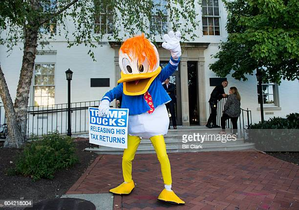 A man in a duck costume waves in front of the Republican National Committee headquarters in Washington as GOP nominee for Vice President Mike Pence...