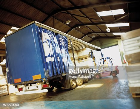 Man in a Forklift Truck Loads an Articulated Freight Lorry in a Warehouse at Immingham Port, Humberside, UK