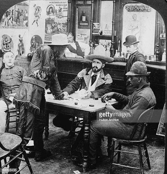 A man in a fringed leather jacket and cowboy hat holds a revolver at his waist as he argues with a seated fellow gambler in a staged photograph...