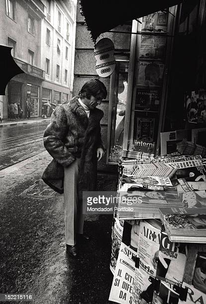 A man in a fur coat standing in front of a newspaper kiosk Milan 1969