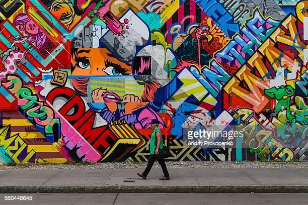 A man in a green shirt walking past a colorful graffiti wall Bowery New York City USA