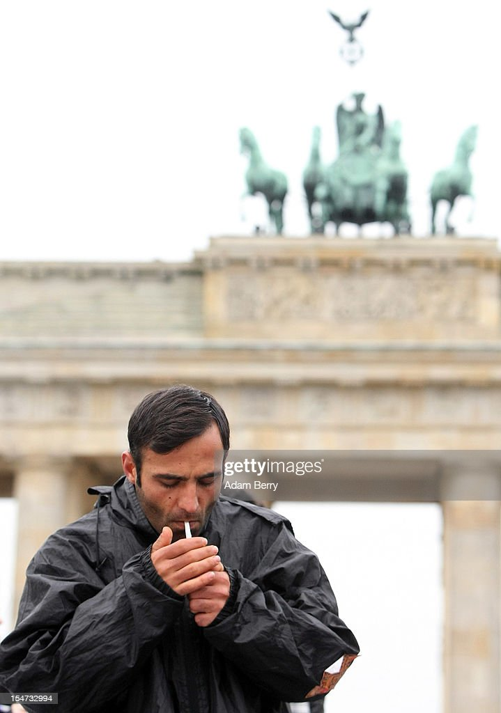 A man in a group of demonstrating refugees and supporters lights a cigarette in front of the Brandenburg Gate on October 25, 2012 in Berlin, Germany. The demonstrators, predominantly from Iran, Afghanistan and Iraq are subsisting on only water, tea and coffee without sugar, and claim to have been told by the police that they are not allowed blankets or tents. They have been sitting in front of the Brandenburg Gate since last night, and say they will continue their strike until the German government responds to their demands for a halt to deportations and faster processing of asylum applications.